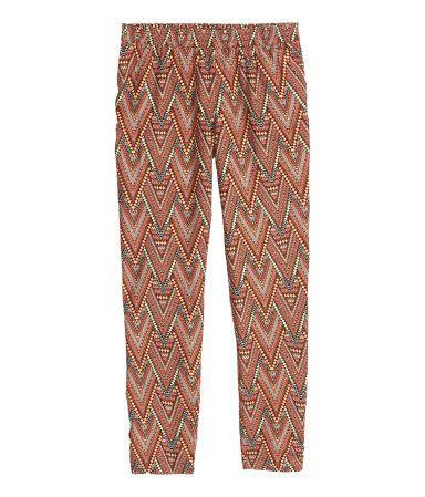 Abrikos/Mønstret. Vide bukser i let, vævet kvalitet. De har elastik i taljen, ben, der bliver smallere forneden, og sidelommer.