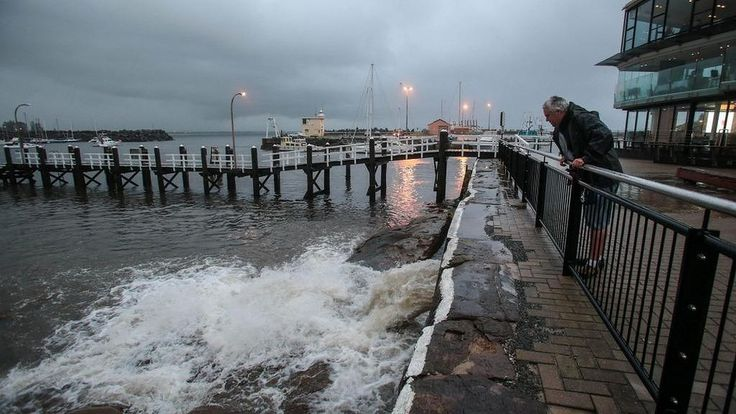David Wisner watches storm water spilling into Wollongong Harbour as heavy rain and strong winds hit the Illawarra.