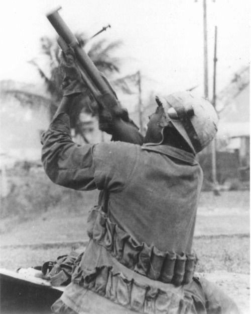 A Marine fires his M79 Grenade Launcher at a sniper's position during the Battle of Hue, 1968.