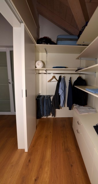 Wardrobe constituted of shelves and chest of drawers. Lacquered matte white finish.