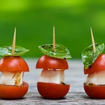 I made these the other night for a small group event.  Use the bottom of the cherry tomatoe for the top and they stand up nicely. Basil toppers with mozarella stick slice.