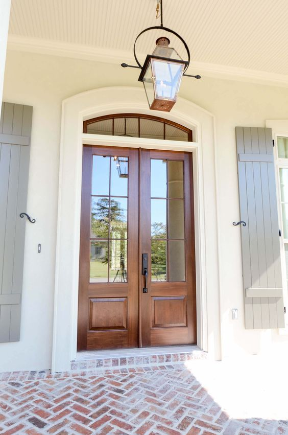 beautiful front entry with wood doors and transom, shutters, and brick porch - via Bevolo
