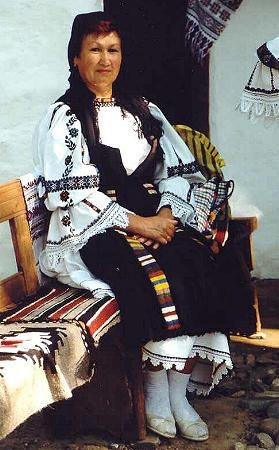 Romanian costume Sălciua - Alba; chemise (Cămaşă cu mâneca din gât) with wide frills (fodor) on sleeves. several vertical rows of embroidery on sleeves in black silk thread, with some red, yellow and blue motifs, and a wide horizontal band of geometric embroidery above the elbow, this style of decoration being known as cămaşă cu şire peste cot. white crochet lace at hem. Pleated black apron (şort), with two vertical rows of embroidery, black lace on the hem. Black fringed scarf called…