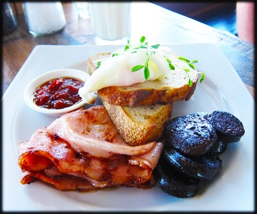 Poached Eggs on fresh Sourdough with smoky, meaty bacon and black pudding — at Pawpaw Cafe in Brisbane.