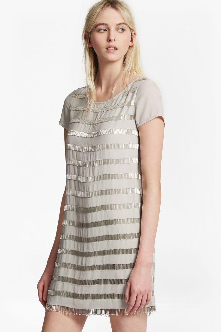 """<ul> <li> Bead-embellished dress</li> <li> Round neck</li> <li> Short sleeves</li> <li> Back zip fastening</li> <li> Tunic fit in mini length — falls freely over the body</li> </ul> <strong>Our lead model is 5ft 10"""" and is wearing a UK size 10 in Freeway Grey. </strong>"""