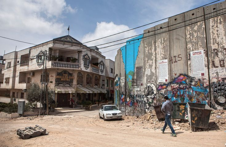 The Walled Off Hotel, opened by the British artist Banksy across an alley from the West Bank wall that separates Israelis from Palestinians, bears witness and whimsy.