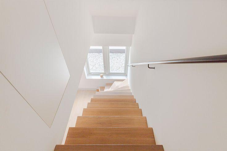 Eiken houten keepboom trap met zwart stalen leuning. De combinatie van wit gestucte wanden en natuurlijk dalicht zorgt voor zowel een frisse als een warme uitstraling.  Ontwerp: BNLA architecten Fotografie: Wim Hanenberg