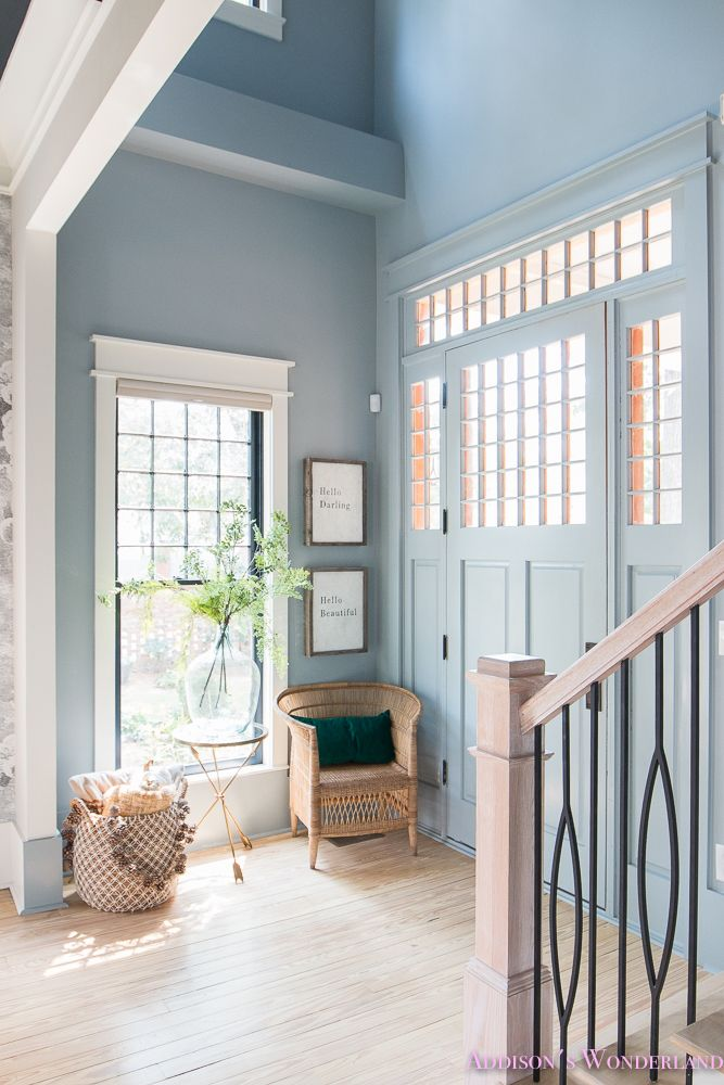 Our small traditional powder blue foyer with Fall decorating ideas with World Market! Fall foyer decorating ideas features light blue gray walls, black window sashes, rattan chair, whitewashed hardwood floors, black stair balusters, alabaster trim and a craftsman front door...