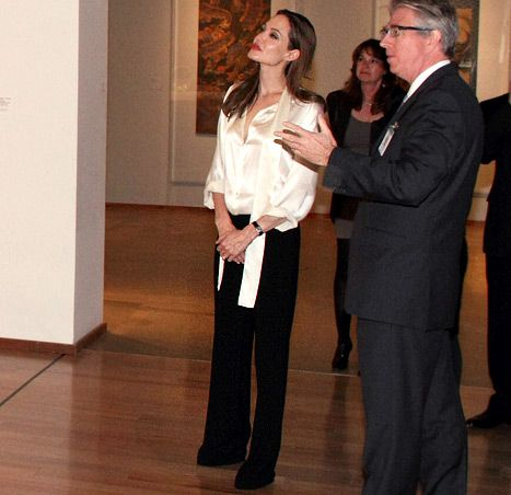 Knowing that her spontaneous engagement ring debut would be documented in a photo that would live on forever, Angelina Jolie made sure to wear a timeless outfit when she, her new fiance Brad Pitt and their son Pax paid a visit to LACMA's Chinese galleries Wednesday.  At the museum, the 36-year-old looked polished in a L'agence ivory tie-neck blouse (which retails for $400) paired with black wide-leg trousers and black heels.