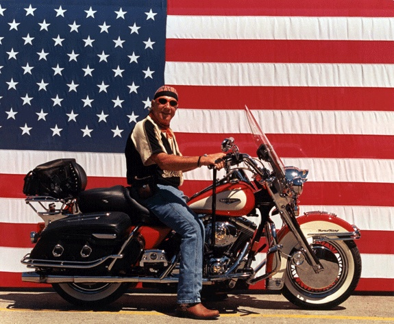 Dad on his Harley at Sturgis in front of Old Glory