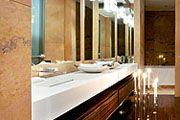 Стены детского санузла и ванной комнаты хозяев облицованы травертином и мрамором. Мебель подчеркивает минималистский стиль этого помещения