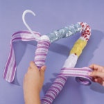 Reuse old plastic bags. Wrap around hanger, tape in place, wrap with ribbon.