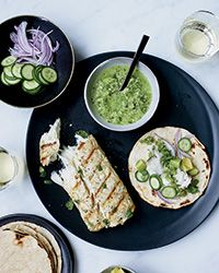 Fish Tacos with Tomatillo Jalepeno Salsa. A delicious salsa you make in a couple of minutes in a blender and a wonderful quick marinade for the fish. Served with warm corn tacos with cucumbers and red onion.