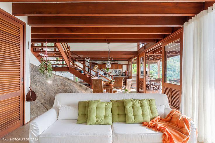 Sofá branco, futons verde e mantinha laranja decoram essa sala de estar em Ilhabela.