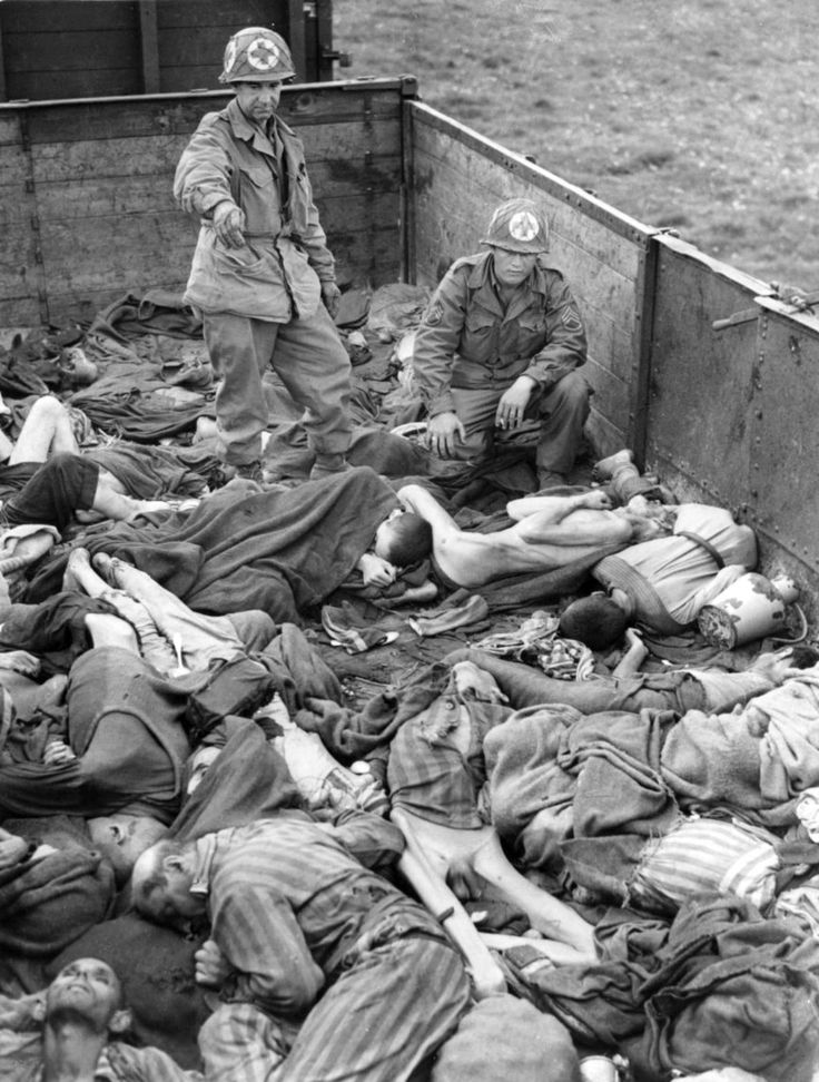 """American Army medics of the Seventh United States Army look over the emaciated corpses in the abandoned """"Dachau death train"""" following the surrender of Dachau concentration camp by the Germans to U.S...."""