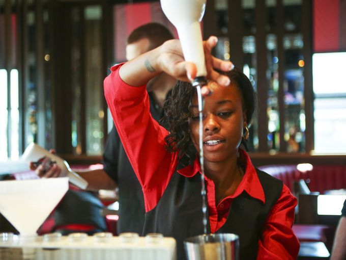 New location, new look for TGI Fridays in Colerain. Photo: Nykee Mitchell of Forest Park practices pouring drinks before a mock session at the new TGI Fridays in the Stone Creek Towne Center Thursday afternoon. The location is the second TGI Fridays to feature a new aesthetic. The Enquirer/Madison Schmidt