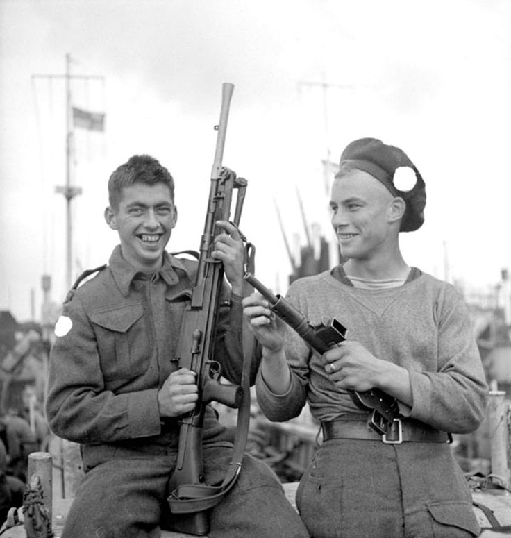 Canadian Infantrymen (left to right) Pvt. Art Robertson of the North Nova Scotia Highlanders and Pvt. Ken Mardon of the Highland Light Infantry aboard an LCI(L) of the 2nd Canadian (262nd RN) Flotilla are photographed in good spirits en route to Juno Beach at Bernières-sur-Mer in France on D-Day; the Allied invasion in Normandy.