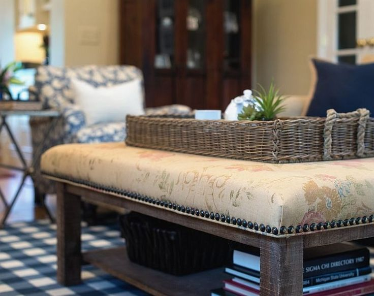 Simple Living Room with Upholstered Coffee Table containing: Wicker Table Tray with Square Pattern Rug also X Leg Accent Table plus Blue Patterned Accent Chair together with Blue Marine Throw with Decorative Book also Unfinished Wood Leg Table