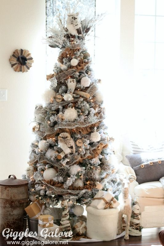 Topped with a snowy owl, this wintry tree is covered in rustic, woodland decor.