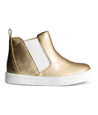 Guld. Ett par sneakers i läderimitation med metallicyta. De har ankelhögt skaft med resår i sidorna och hälla bak. Foder och innersula i textil. Yttersula i