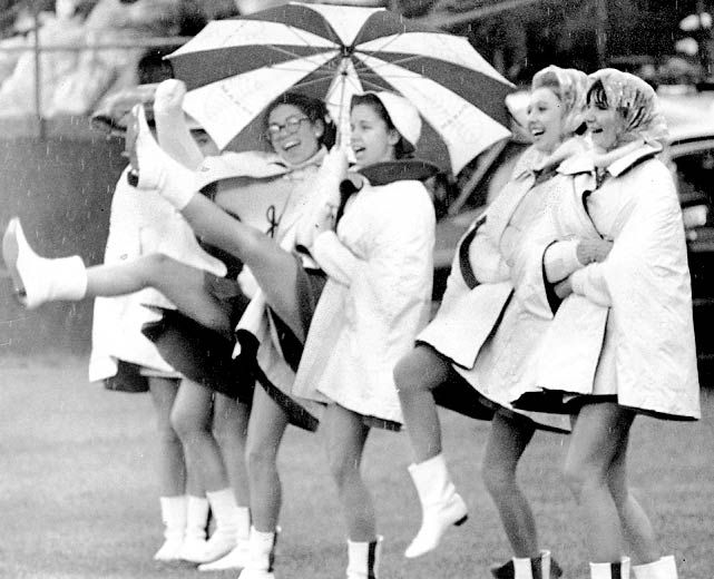 vintage photo of New York Jets girls high steppin' in the rain, in go go boots