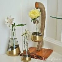 Labratory-beakers-painted-with-gold-paint-and-a-recycled-banana-hook-make-a-fun-display-for-flowers