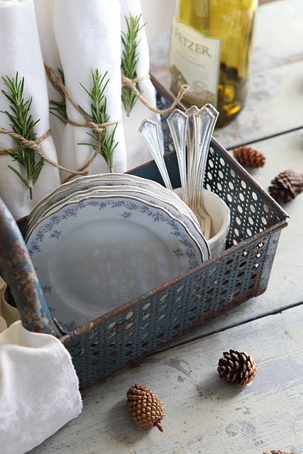 rosemary sprigs. white napkins. blue china. pine cones.