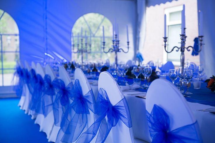 Witte stoelen met blauwe strik van tule. Een gedekte tafel voor een diner met het thema blauw. Opgezet in een tent met daarin blauwe vloerbedekking.