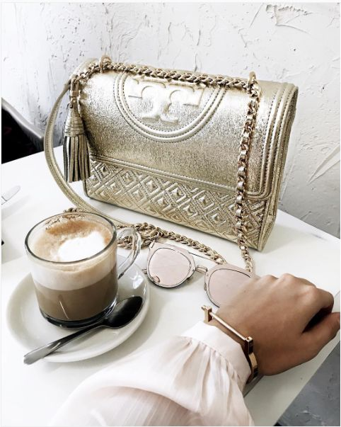 Emily Luciano takes a coffee break with her Tory Burch Fleming Metallic Small Convertible Shoulder Bag