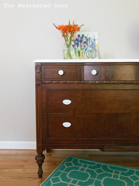 The Weathered Door: A dark wood dresser with a white top
