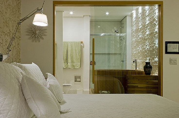 Uma porta de correr de vidro transparente e madeira, separa o quarto do banheiro, deixando o ofurô e a bela parede com textura em evidência. Projeto e foto: Ana Paula BarrosAna Paula Barros.