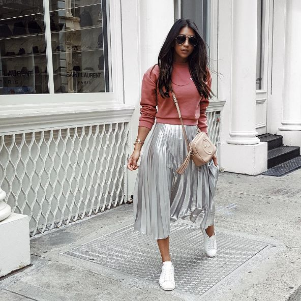 How to copy 7 of the best fashion blogger outfits from New York Fashion Week: dress down a pleated metallic skirt by styling it with a crewneck sweatshirt and white sneakers