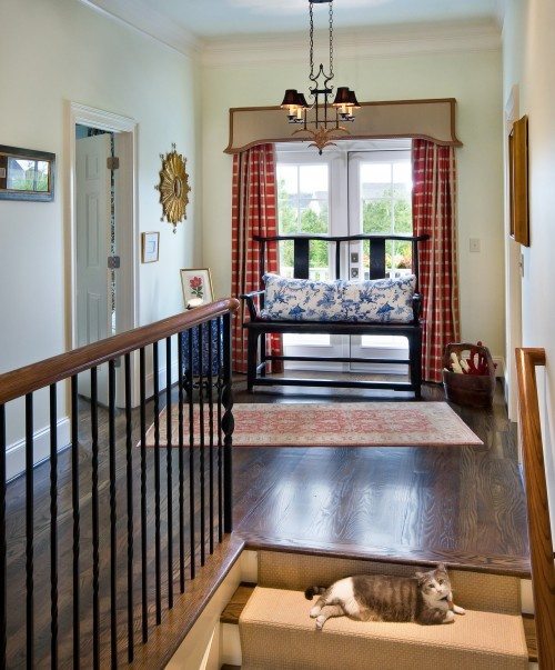 Americana.  This is very appealing to me but the crooked rug kinda tugs at my OCD side....love the curtains and the cat on the top step! :)