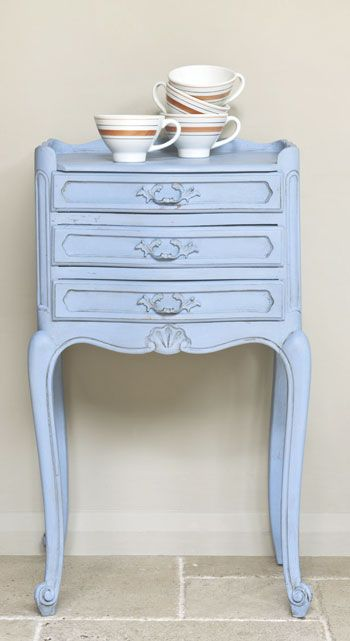 A shapely curvy cabriole legged side table with a shell in the centre a shell typical motif.  It's a modern piece  painted it in Louis Blue.