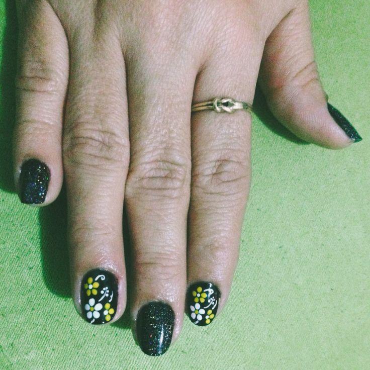Uñas esmalte negro, decorado de flores en blanco y amarillo