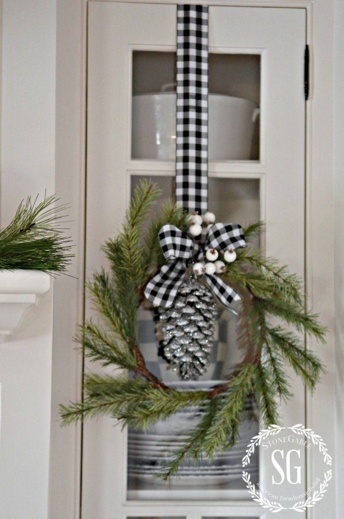 pine wreath with white berries, black and white check ribbon, silver glittered pinecone hanging in center. Great look.