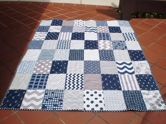 This stunning nautical themed patchwork baby quilt measuring 36 by 48 in grey and navy blue featuring anchors and waves as well as chevrons, polka dots, and stripes would be perfect as a lap quilt or for the nursery for either a boy or a girl; newborn, infant or toddler (FYI: crib mattress measures 27 by 52).  As a traditional 3 layered quilt:  The quilt top, made of 100% cotton designer fabrics including Riley Blake, is machine pieced.  A middle layer of cotton batting has been added for…