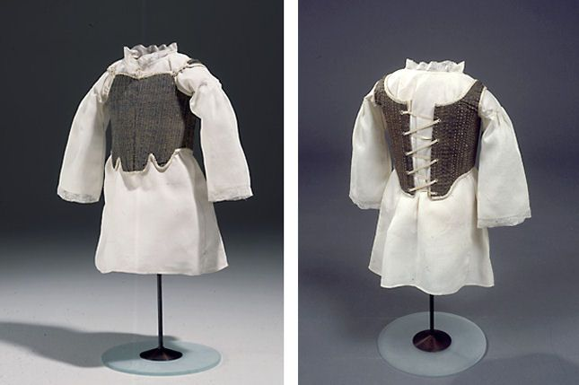 Chemise and corset of an 18 month old girl, ca.1760,  Denmark. Chemise has drawstring at the neck, Lace to neck and cuff is probably an imitation of Flemish lace. The corset is boned but with the boning set further apart than in an adult corset and is laced in the back. NATMUS DK