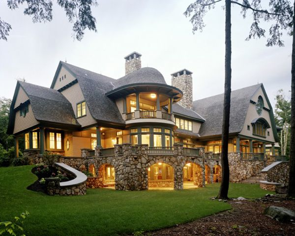 Light on House Front View Sumptuous Fairytale House Inspired by the Natural Landscape. Rounded column windows and porch seating area. Elevated deck, second story balcony.