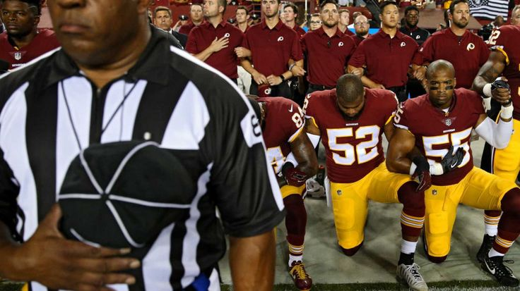 Ryan Anderson #52 of the Washington Redskins locks arms with teammates as they kneel and stand in unison during the national anthem before playing against the Oakland Raiders at FedExField on September 24, 2017 in Landover, Maryland