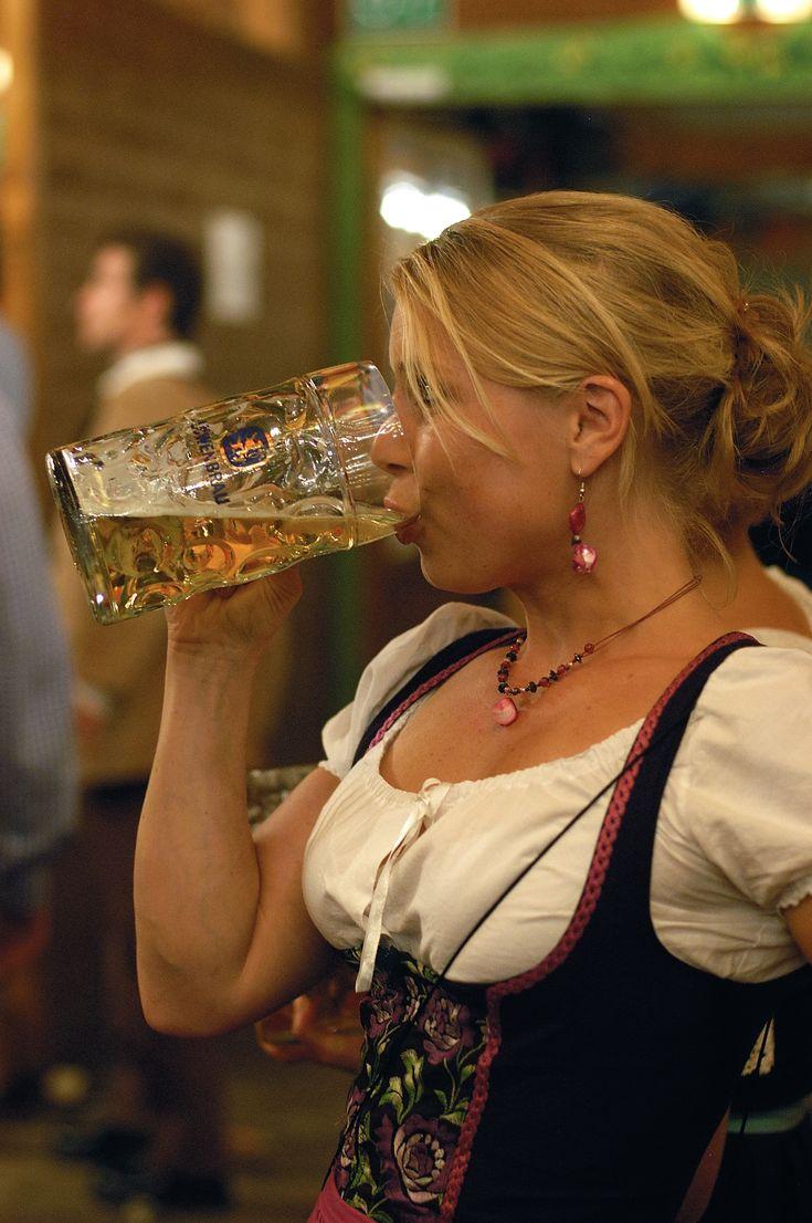 A beer-drinking woman at Oktoberfest in Munich wearing a dirndl