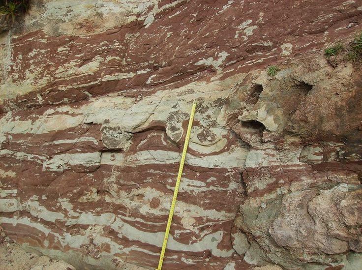 """Praia do Baleal: nível argiloso com tonalidades vermelhas e acinzentadas da """"Formação grés superiores com vegetais e dinossáurios"""" (FRANÇA et al., 1960), do Jurássico Superior, evidenciando """"figuras de carga""""."""
