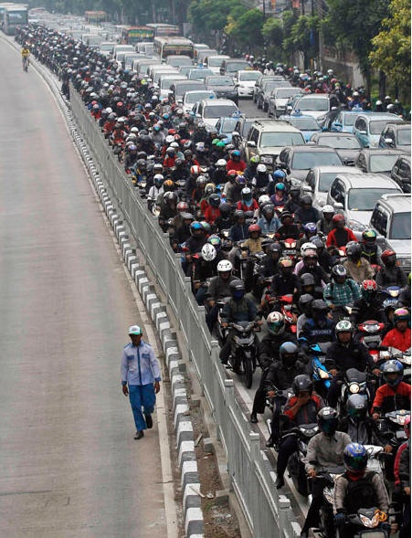 A man walks in a bus lane next to a morning rush hour traffic jam in Jakarta.