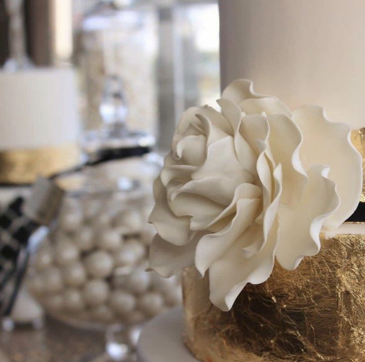 White and gold event styling at Berth . The dessert table features white chocolate strawberry  tower, cup cakes and themed party sweets. Gorgeous cakes with iced roses