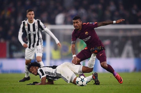 Barcelona's Brazilian midfielder Paulinho (R) vies with Juventus' forward from Colombia Juan Cuadrado during the UEFA Champions League Group D football match Juventus Barcelona on November 22, 2017 at the Juventus stadium in Turin.  / AFP PHOTO / Marco BERTORELLO
