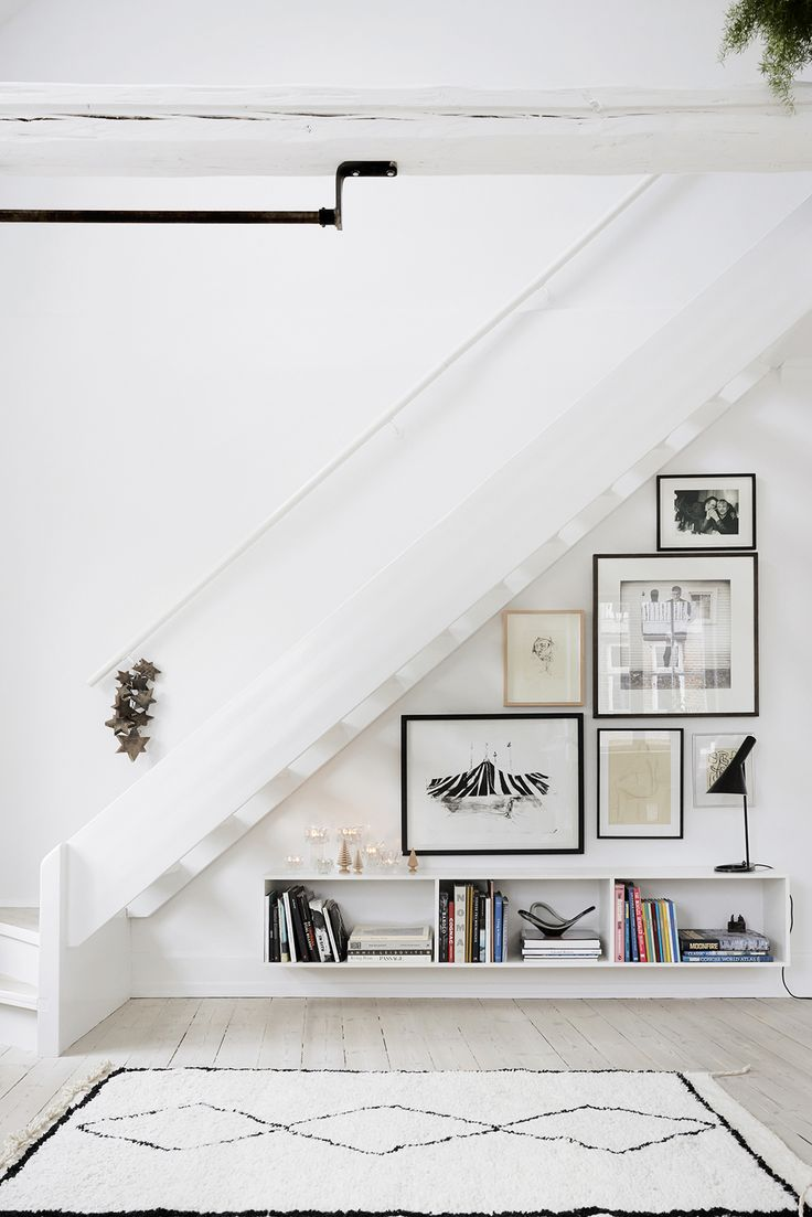 simple white stair landing with moroccan rug and art wall | via coco kelley