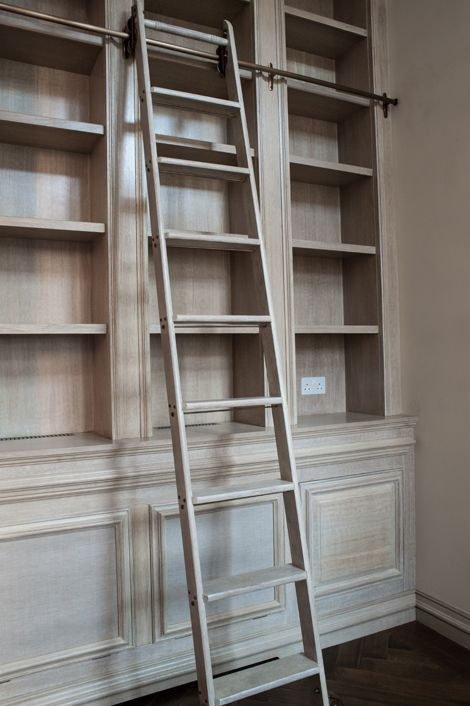 Design & Finish Library bookcase made in limed oak; designed, made, finished and fitted by Rupert Bevan ltd. With internal lighting along all the shelving, and a matching rolling ladder on fixed patinated brass rail, with patinated brass brackets