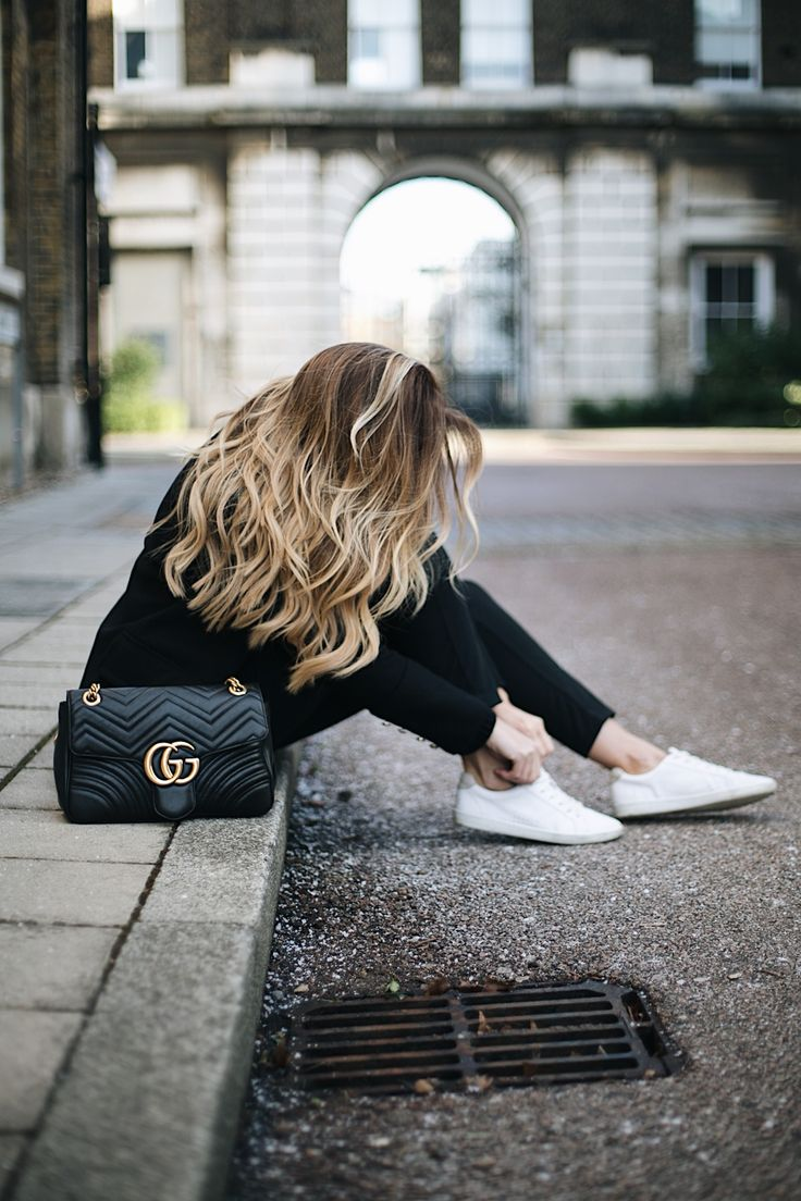 Emma Hill wears Gucci Marmont bag, black tailored trousers, black military jacket, white trainers, chic all black winter outfit