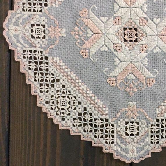 Este tapete hardanger precioso, hecho a mano es cosida en una tela azul grisáceo con hilos blancos y rosas. Cuenta con muchos detalles delicados y mide 11.5x11.5 aprox.