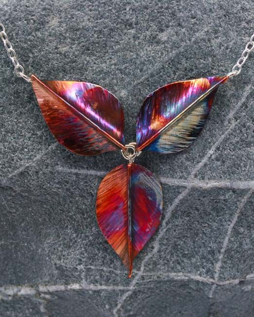 """Necklace with multi coloured handmade copper leaf pendant on silver chain. Hand crafted, sawn and hammered copper leaf pendant with heat patina. The leaves are approx. 25mm x 15mm. They hang from a silver chain with an overall length of 17"""" and a drop of 40mm.  Please note: Copper will naturally darken with age.  #copper #leaf #pendant #silver"""